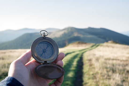 A hand holding a compass and walking down a path towards the mountains
